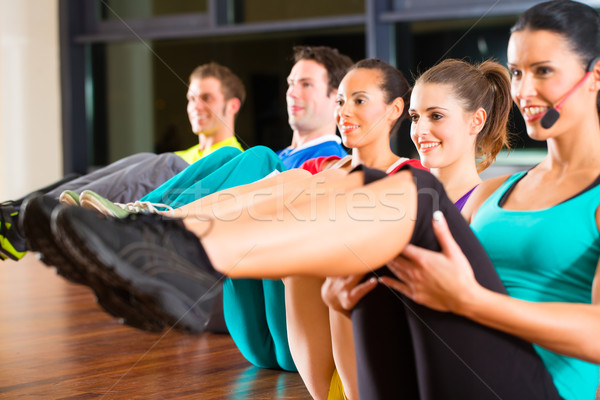 Group of people and instructor in gym stretching Stock photo © Kzenon