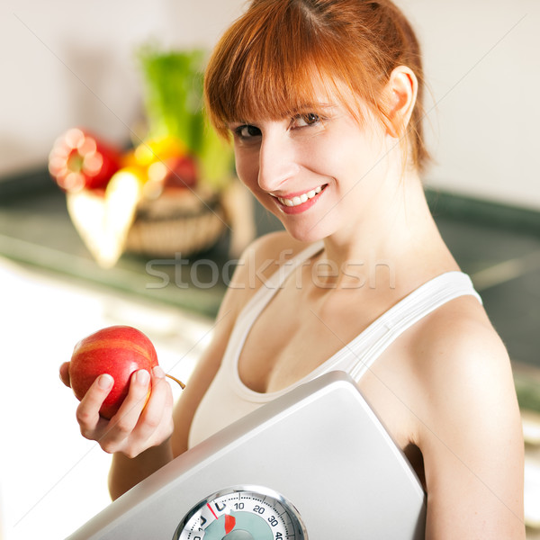 Stock photo: loosing weight - woman with scale and apple