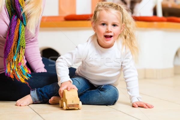 Menina jogar brinquedo de madeira carro sessão mãe Foto stock © Kzenon