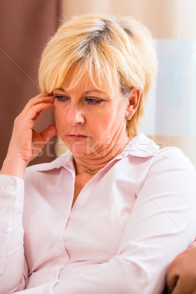 Senior touching forehead having headache or pain Stock photo © Kzenon