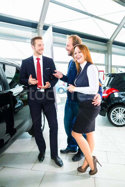 Dealer, clients and auto in car dealership Stock photo © Kzenon