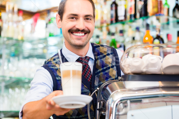 Barista in coffee bar offers latte macchiato in glass Stock photo © Kzenon