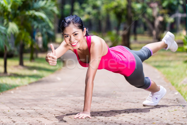 Proud and successful woman doing sport push-up Stock photo © Kzenon