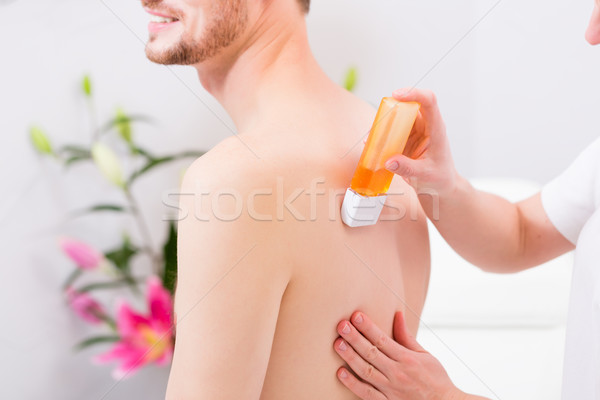 man at waxing hair removal in beauty parlor Stock photo © Kzenon