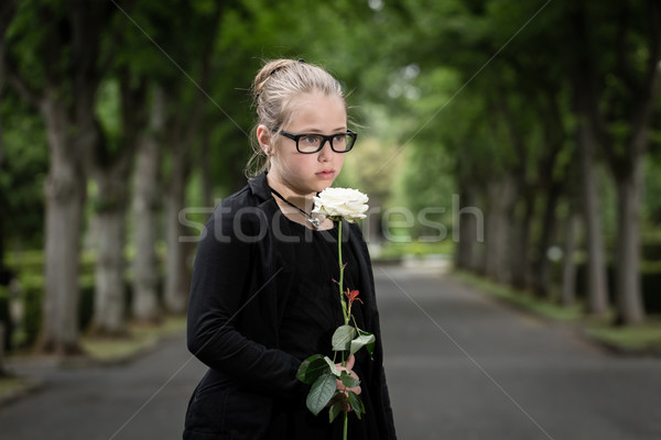 girl with white rose mourning deceased on graveyard Stock photo © Kzenon