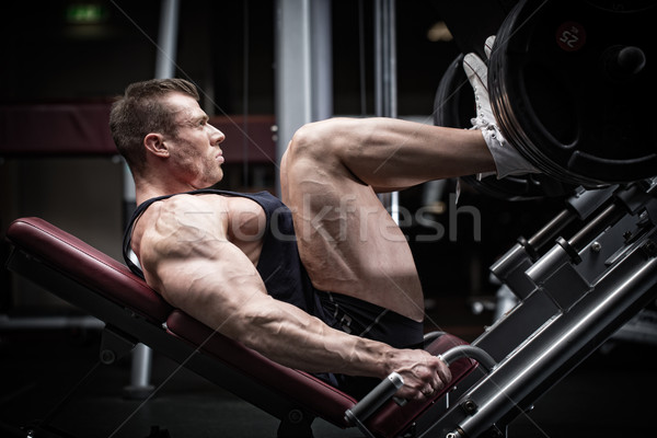 Man in gym training at leg press Stock photo © Kzenon