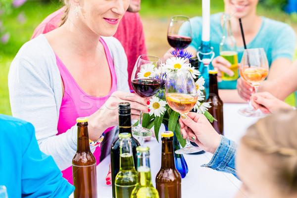 Friends celebrating small garden party clinking glasses Stock photo © Kzenon