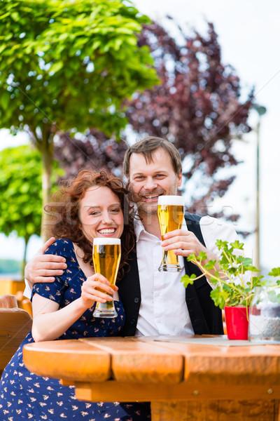 Man and woman drinking in beer garden pub Stock photo © Kzenon