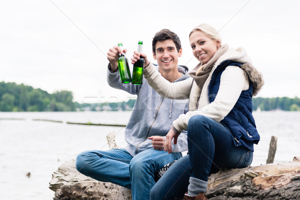 couple sitting on tree stump at the riverside drinking beer  Stock photo © Kzenon