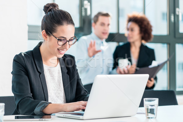 Young woman smiling while using a laptop in the office Stock photo © Kzenon