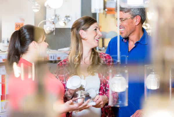 Clerk giving advice about lamps to couple in hardware store Stock photo © Kzenon