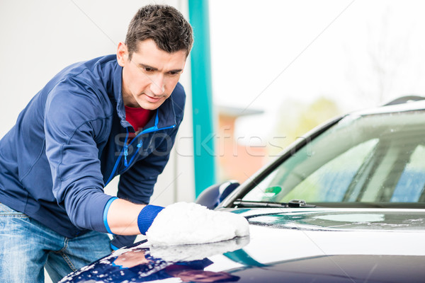 Hard-working man polishing car with white microfiber mitt Stock photo © Kzenon
