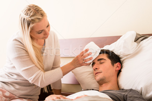 Woman holding a compress on the forehead of her partner Stock photo © Kzenon