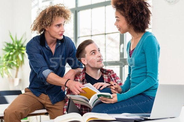 Tre studenti informazioni due diverso libro di testo Foto d'archivio © Kzenon