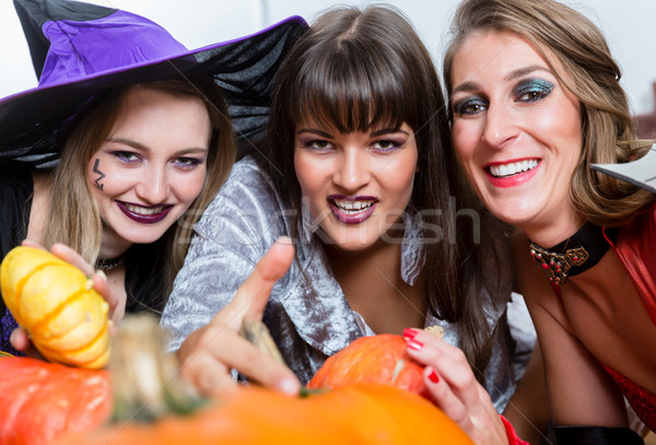 Stock photo: Three beautiful women acting as witches joining their malicious