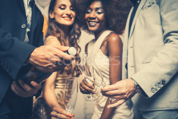 Man opening champagne bottle on celebration in club Stock photo © Kzenon