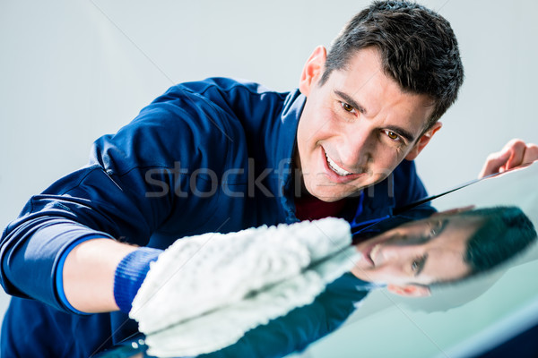 Cheerful young worker polishing car with soft microfiber mitt Stock photo © Kzenon