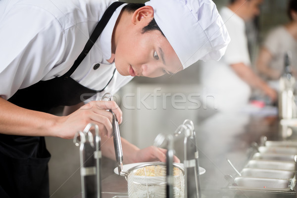 Young Asian chef plating food in a restaurant Stock photo © Kzenon