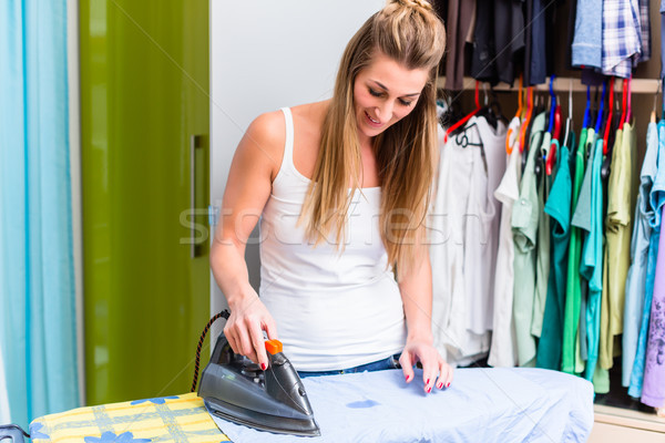 Young woman in front of wardrobe ironing the laundry Stock photo © Kzenon
