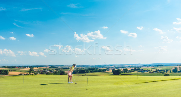 Determined young woman practicing golf on the grass of a training area Stock photo © Kzenon