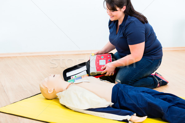 First aider trainee learning revival with defibrillator Stock photo © Kzenon