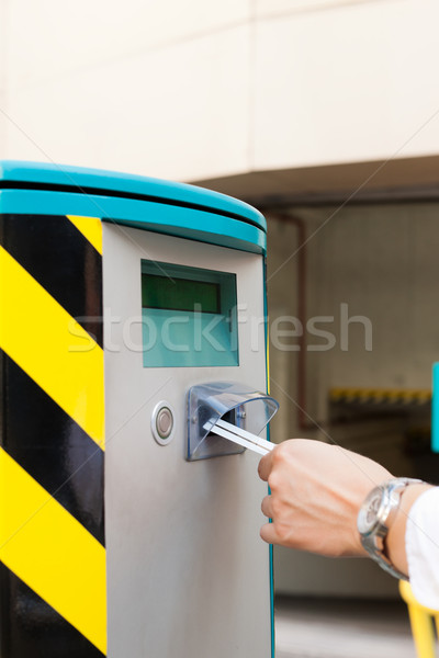 Hand is inserting parking ticket into barrier of garage Stock photo © Kzenon