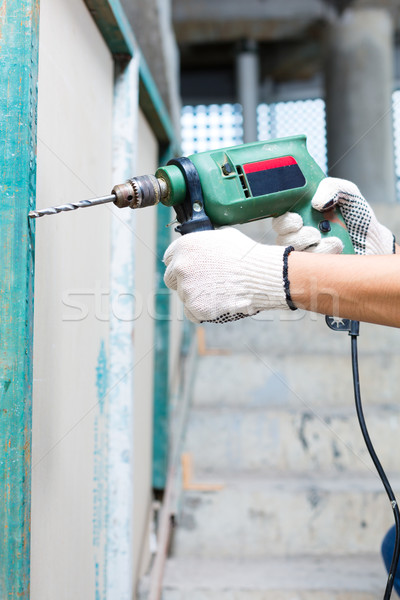 worker drilling with machine in construction site wall Stock photo © Kzenon