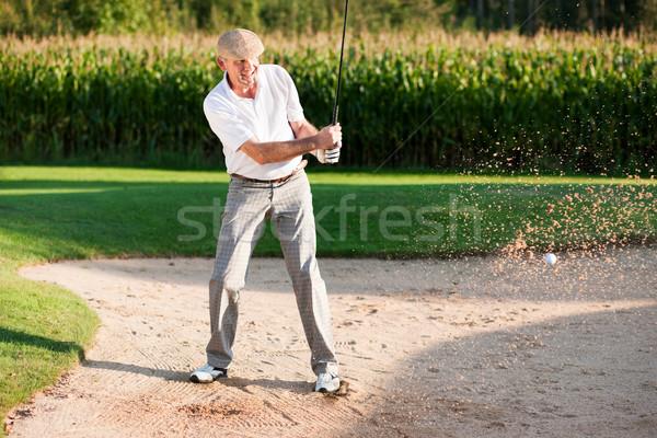 Senior golf player in sand trap Stock photo © Kzenon