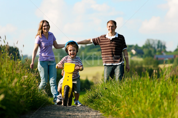 Active family in summer walking and bicycling Stock photo © Kzenon
