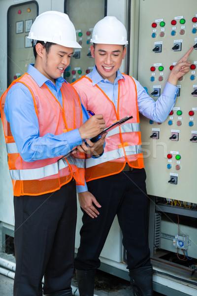 Asian technicians at panel on construction site Stock photo © Kzenon