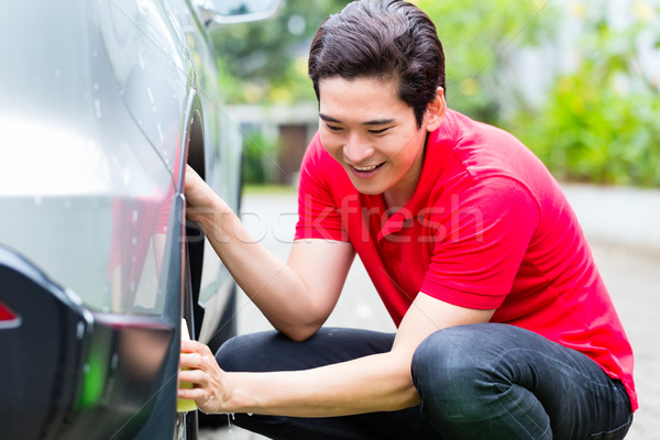 Asian man cleaning car rims with sponge Stock photo © Kzenon