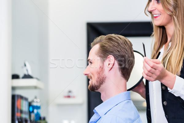 Haircutter showing customer the new cut Stock photo © Kzenon