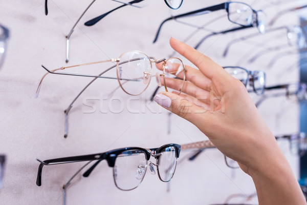 Woman taking glasses out of shelf in optician store Stock photo © Kzenon