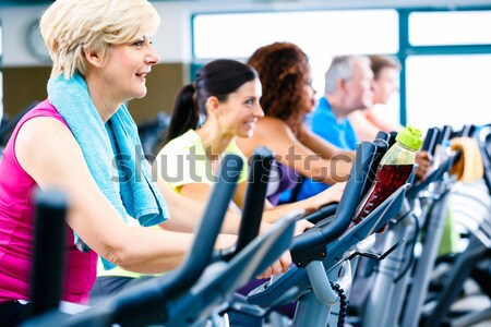 Group of men and women doing cardio training in gym Stock photo © Kzenon