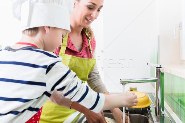 Mom washing-up the crockery, son helping Stock photo © Kzenon