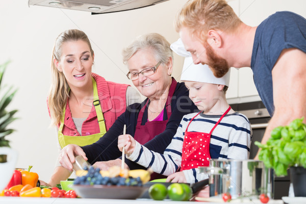 Family cooking in multigenerational household with son, mother,  Stock photo © Kzenon