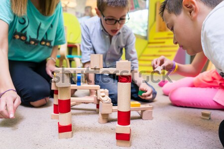 Female educator teaching children to build a train circuit durin Stock photo © Kzenon