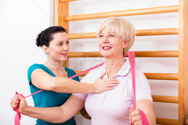 Physio assisting elderly woman during exercise with power band a Stock photo © Kzenon
