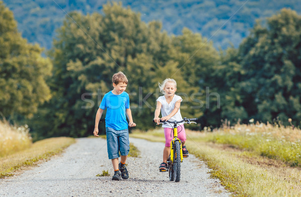 Boy and girl walking and riding bicycle on a dirt path Stock photo © Kzenon