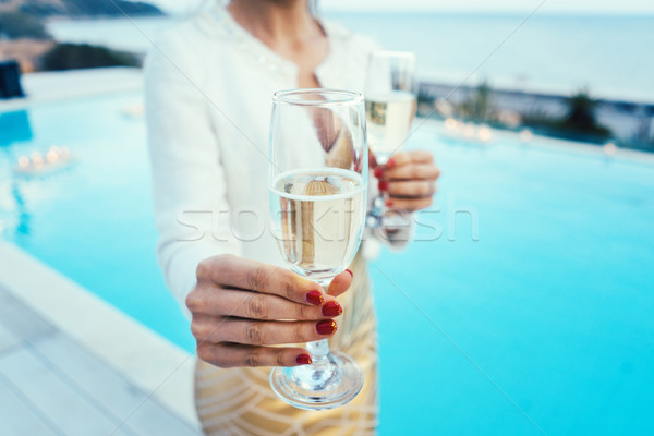 Woman handing glass of sparkling wine at pool and beach party Stock photo © Kzenon