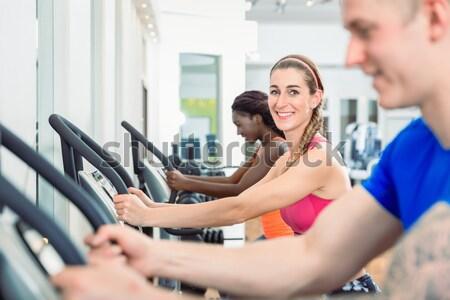 Woman smiling running on treadmill in the gym modern health club Stock photo © Kzenon