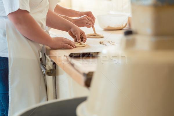 Close-up on baker in bakery forming pretzel bread Stock photo © Kzenon