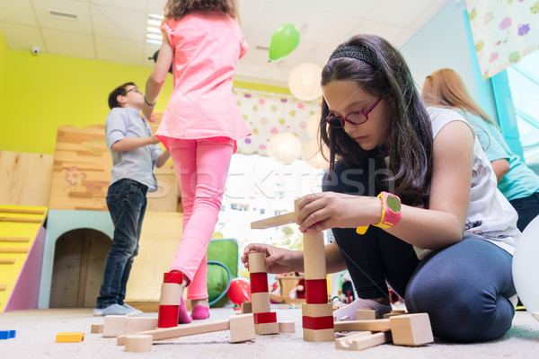 Cute girl building a structure in balance during playtime at the kindergarten Stock photo © Kzenon