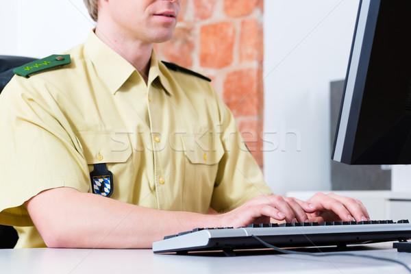 Police Officer working on desk in department Stock photo © Kzenon