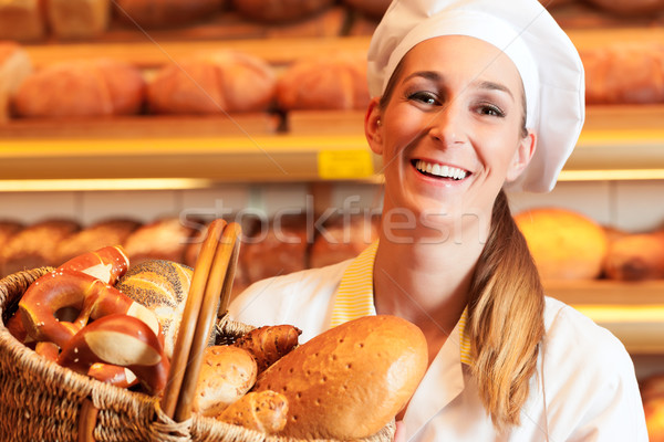 Female baker in bakery selling bread by basket  Stock photo © Kzenon