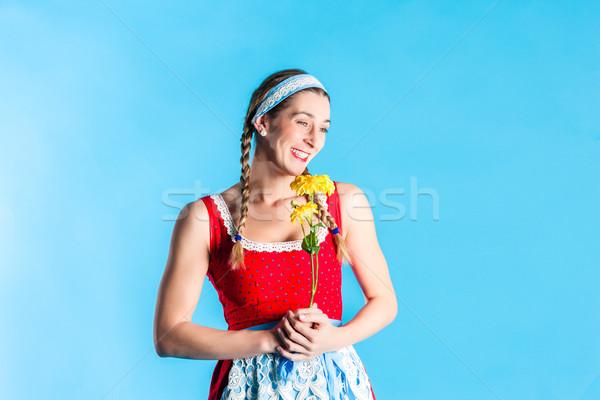 Woman in dirndl dress holding flowers Stock photo © Kzenon