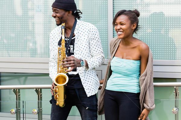 Afrikai pár játszik szaxofon zene mosoly Stock fotó © Kzenon