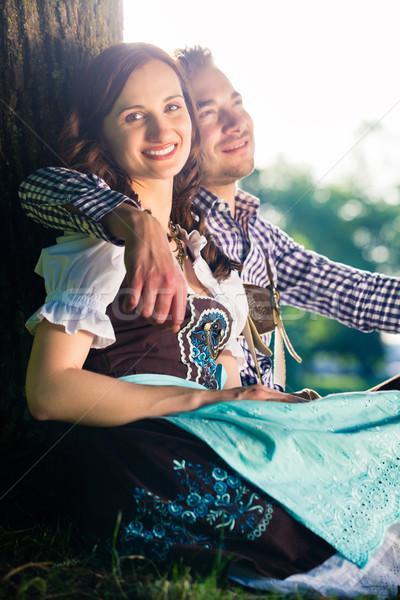 Bavarian couple in Tracht hugging under tree Stock photo © Kzenon