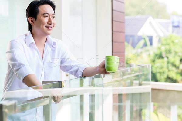 Chinez om balcon acasă cafea dimineaţă Imagine de stoc © Kzenon
