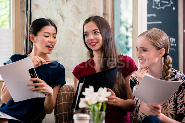 Young women holding files in a coffee shop Stock photo © Kzenon